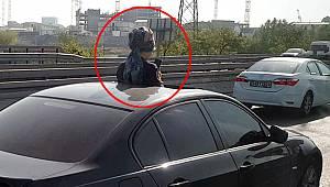 Aracın sunroof'undan çıkan kadın telefonla oynadı